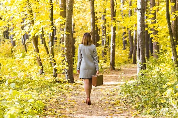 가을 공원에서 산책하는 복고풍 가방을 가진 젊은 세련된 여자의 뒷면