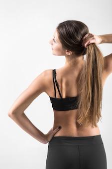彼女の髪を腕に持っている若い女性の背中の眺め