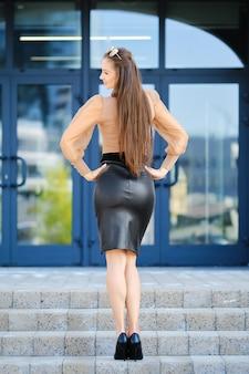 オフィスビルの近くの階段に立っているブラウスと革のスカートの若い女性の背面図