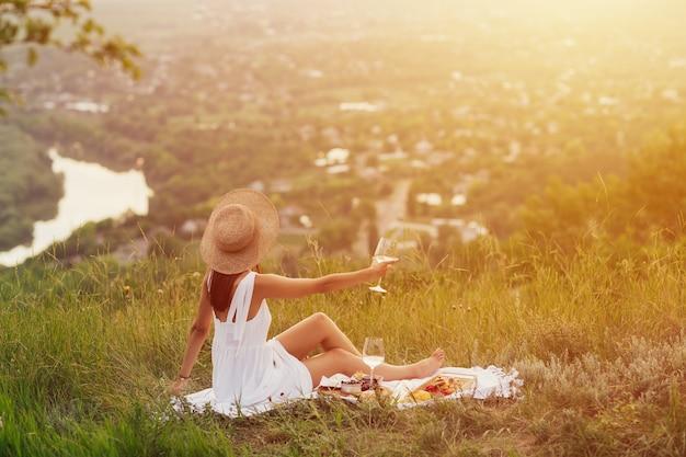 エレガントな白いドレスと麦わら帽子でリラックスして夏の夕日を楽しんでいる若い女性の背面図。