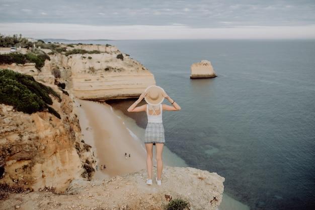 Вид сзади молодой женщины в шляпе и милом летнем платье, стоящей на камне