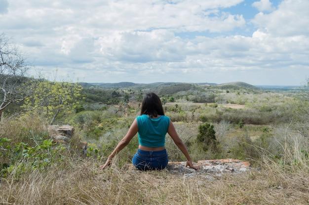 Вид сзади молодой женщины, смотрящей на горизонт с высоты холма