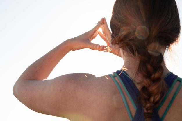 Вид сзади молодой женщины, медитации на открытом воздухе