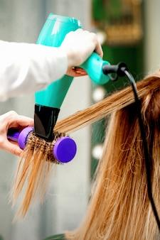 Вид сзади молодой женщины, получающей сушку волос феном и расческой в парикмахерской