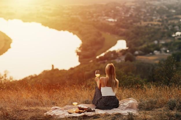 リラックスして秋の夕日を楽しんでいる若い女性の背面図。自然のピクニックの女性。
