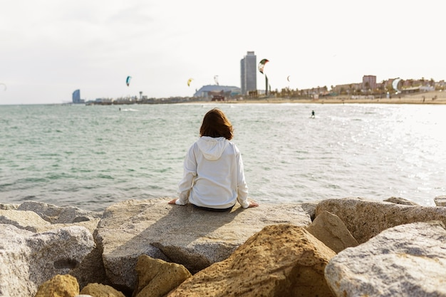 Вид сзади молодой женщины, отдыхая на берегу моря
