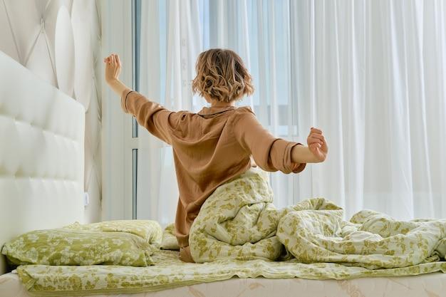 Вид сзади молодой женщины, протягивающей руки, сидя на кровати в домашней спальне, глядя в окно