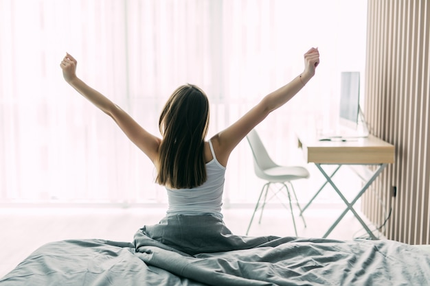 Вид сзади молодой женщины, растягивающейся на неубранной кровати после пробуждения и смотрящей на город в окне