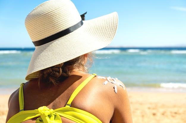 彼女の肩に太陽の形の日焼け止めクリームでビーチで日焼けの若い女性の背面図