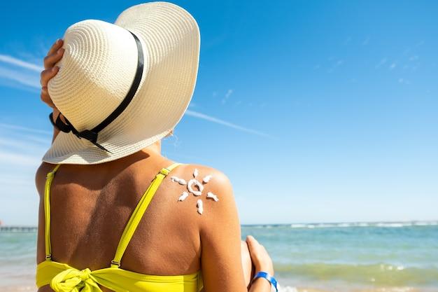 彼女の肩に太陽の形の日焼け止めクリームでビーチで日焼けする若い女性の背面図。