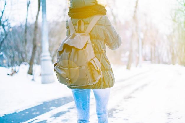 巨大なバックパックと信じられないほどのwinterorestを歩いている若い女性の背面図