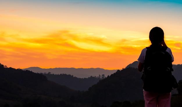 Вид сзади молодой женщины, наблюдая красивый закат над горным слоем