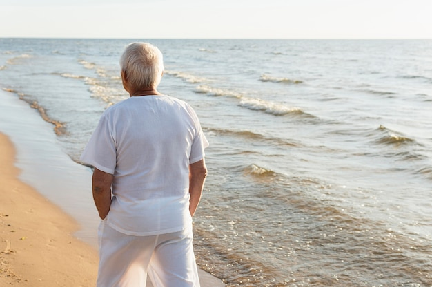 Back view of older man spending his time at the beach