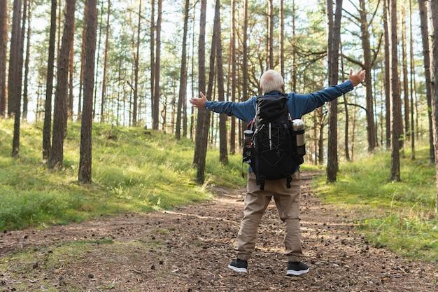 Vista posteriore dell'uomo più anziano con le braccia aperte per godersi la natura