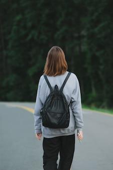 針葉樹林の近くを歩く観光客の女の子の背面図