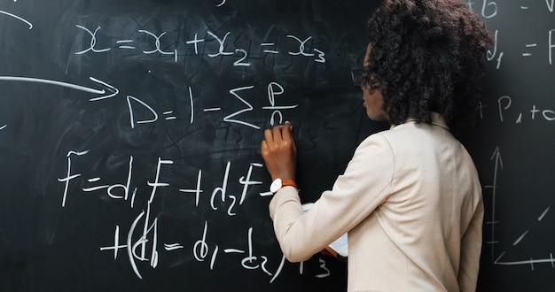 黒板に数式や数学の法則を書く学校のアフリカ系アメリカ人の若い女性教師の背面図。学校のコンセプト。物理法則を説明する眼鏡の女性講師。リア。