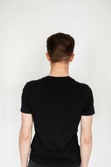 스튜디오의 흰색 바탕에 세련된 검은색 티셔츠를 입은 세련된 짧은 머리를 한 공정한 머리 청년의 뒷모습. 세련된 남자가 벽을 마주보고 서 있습니다. 사진 모델에 대한 스냅.