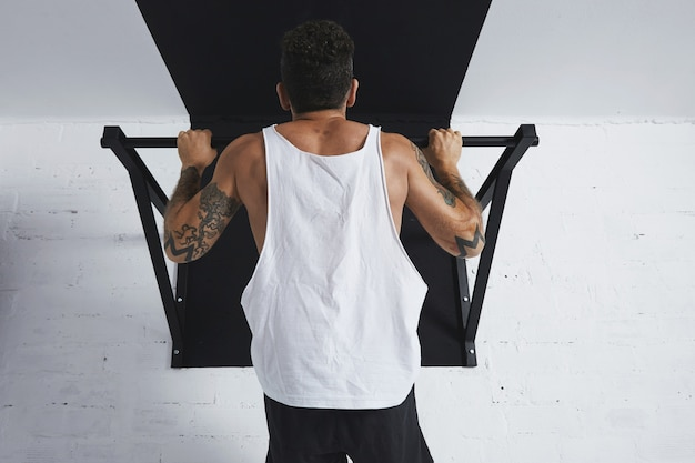 흰색 빈 탱크 티셔츠에 근육질 남성 운동 선수에 대한 다시보기 calisthenic 움직임을 보여주는 상단에 들고 풀 바를 당겨