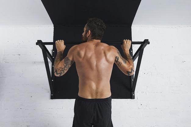 근육질의 토플리스 남성 운동 선수에 대한 뒷모습 calisthenic 움직임을 보여주는 풀 바를 위로 당기고 머리는 왼쪽 방향을 봅니다.