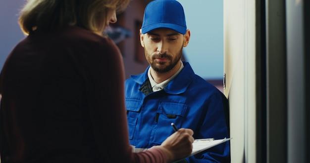 郵便配達員から宅配便を持っているときにクリップボードに署名する白人女性の背面図。