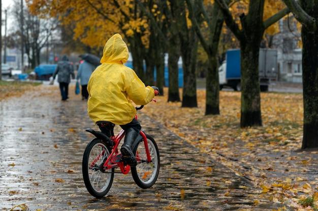 Вид сзади на ребенка в желтом плаще. мальчик едет на велосипеде в осеннем парке под дождем.