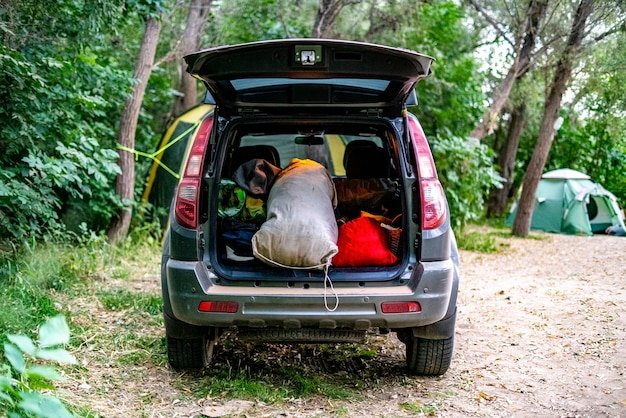 Back view of opened car trunk packed full of luggage bags in nature campp.