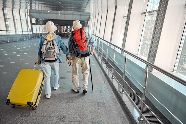 뒷모습 또는 트롤리 가방이있는 고위 여성과 걷는 지팡이가있는 남편