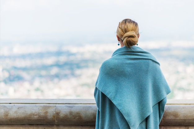 Back view of pensive lonely young woman in blue clothes looking into the distance with hope.