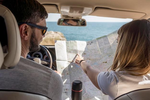 新しい目的地を見つけるために地図を見ている人々を後ろから見る