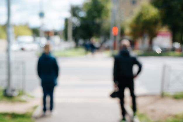 Вид сзади люди стоят на пешеходном переходе перед красным светофором на открытом воздухе, расфокусировать.