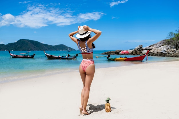 Back view: the perfect girl posing beach.   of travel. beautiful female model with tropical fruit near with her. thai boats on the
