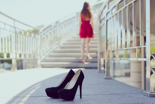 Back view photo of girl in red dress climbing stairs barefoot and highheels