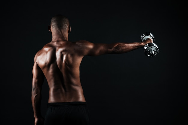 Back view photo of half-naked muscular sports man, with dumbbell in right hand