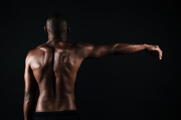 Back view photo of half-naked muscular sports man, with right hand up