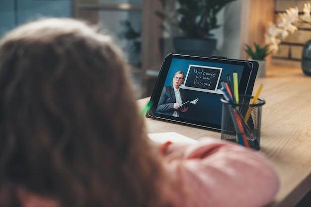 Вид сзади фото кавказской девушки, сидящей за столом и слушающей урок учителя на планшете