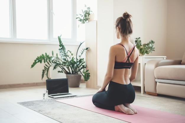床のラップトップの前で瞑想しているスポーツウェアの白人スポーティな女性の背面図の写真
