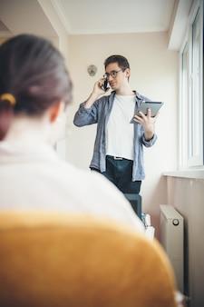 Вид сзади фото кавказской женщины, сидящей в кресле, пока ее деловой партнер разговаривает по телефону с планшетом в руке