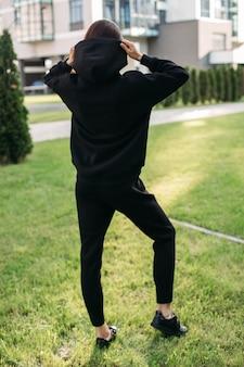手でフードを保持しながら黒のスポーツウェアとスニーカーを身に着けているスタイリッシュな女性の背面写真。女性のファッション。都市のライフスタイル