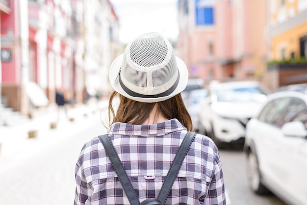帽子のカラフルな家の背景の女性の背面図の写真