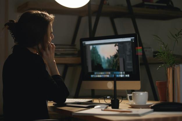 Вид сзади фото молодой женщины дизайнер разговаривает по телефону.