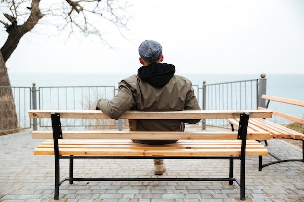 Вид сзади картина молодого африканского человека на скамейке