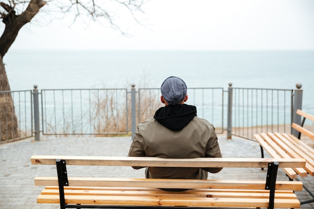 Back view picture of young african man on a bench