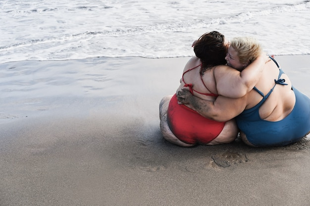 Back view of plus size women sitting on the beach hugging each other during summer vacation - focus on right face
