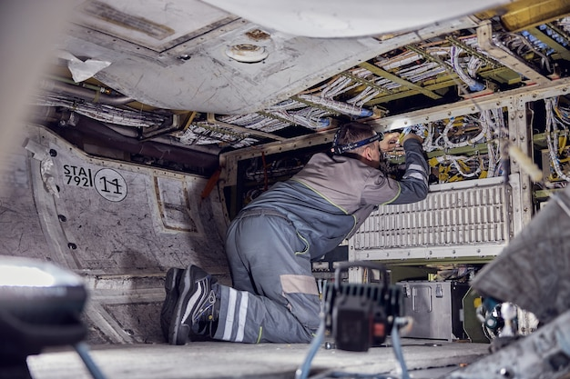 Back view portrait of adult engineer in overall uniform being on your knees inside the fuselage while working with electrical system on passenger aircraft
