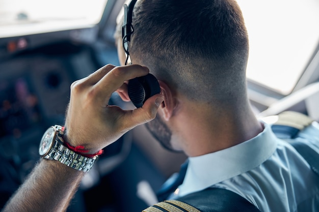 Back view portrait of bearded pilot with watch on hand while touching his headphone in the cockpit of aircraft