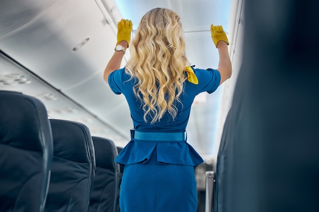 Back view portrait of beautiful female air hostess in blue uniform showing airplane rules for safety on board