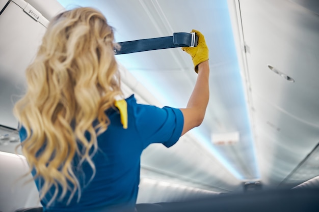Back view portrait of blonde european air hostess in blue uniform holding belt in hands while showing it in the board of passengers aircraft