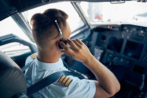Back view portrait of confident pilot in uniform with headphones while he is working on the cabin