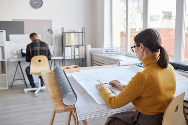 Back view portrait of female architect drawing blueprints while sitting by desk in office,