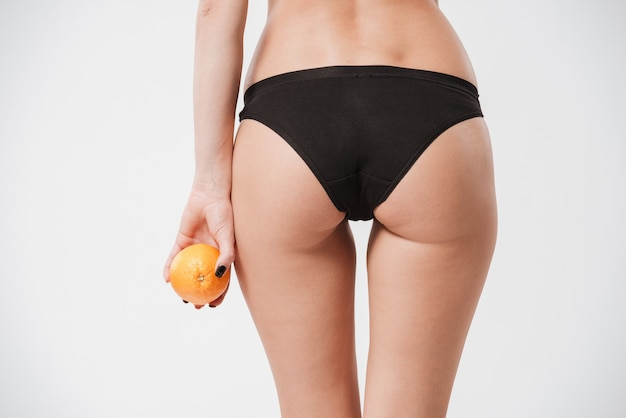 Back view portrait of a fit female ass in black underwear holding orange isolated